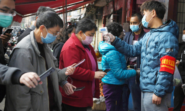 People scanning a QR code on their phones while volunteers check their temperatures before entering a market in Kunming, in China's southern Yunnan Province | Photo by Wong Campion, Reuters